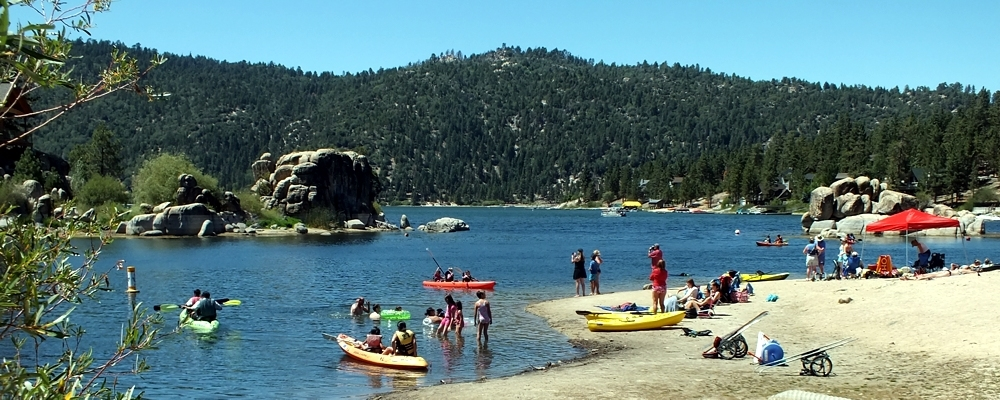 people boating and playing in the sand at big bear lake