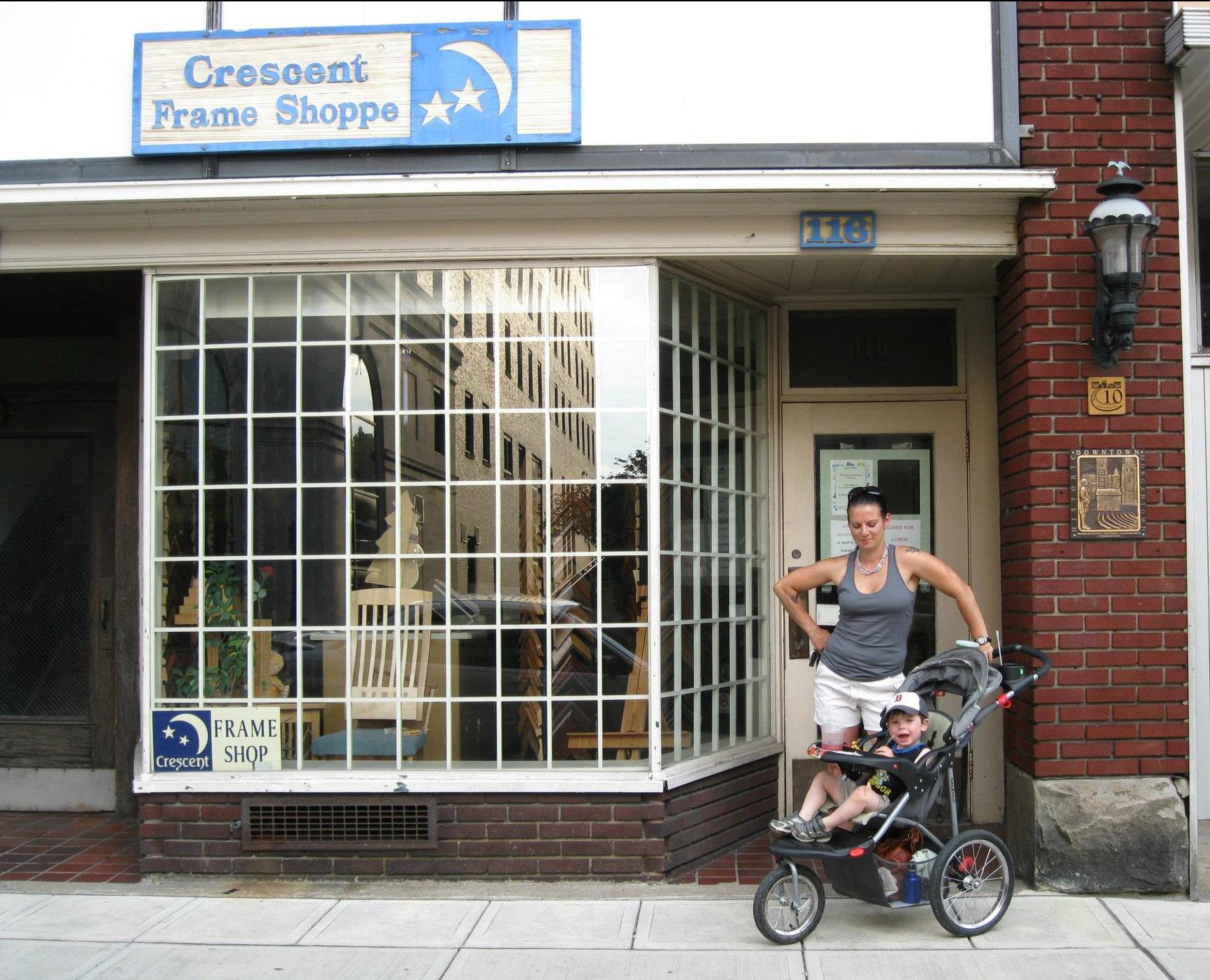 woman and baby in stroller infront of crescent frame shoppe