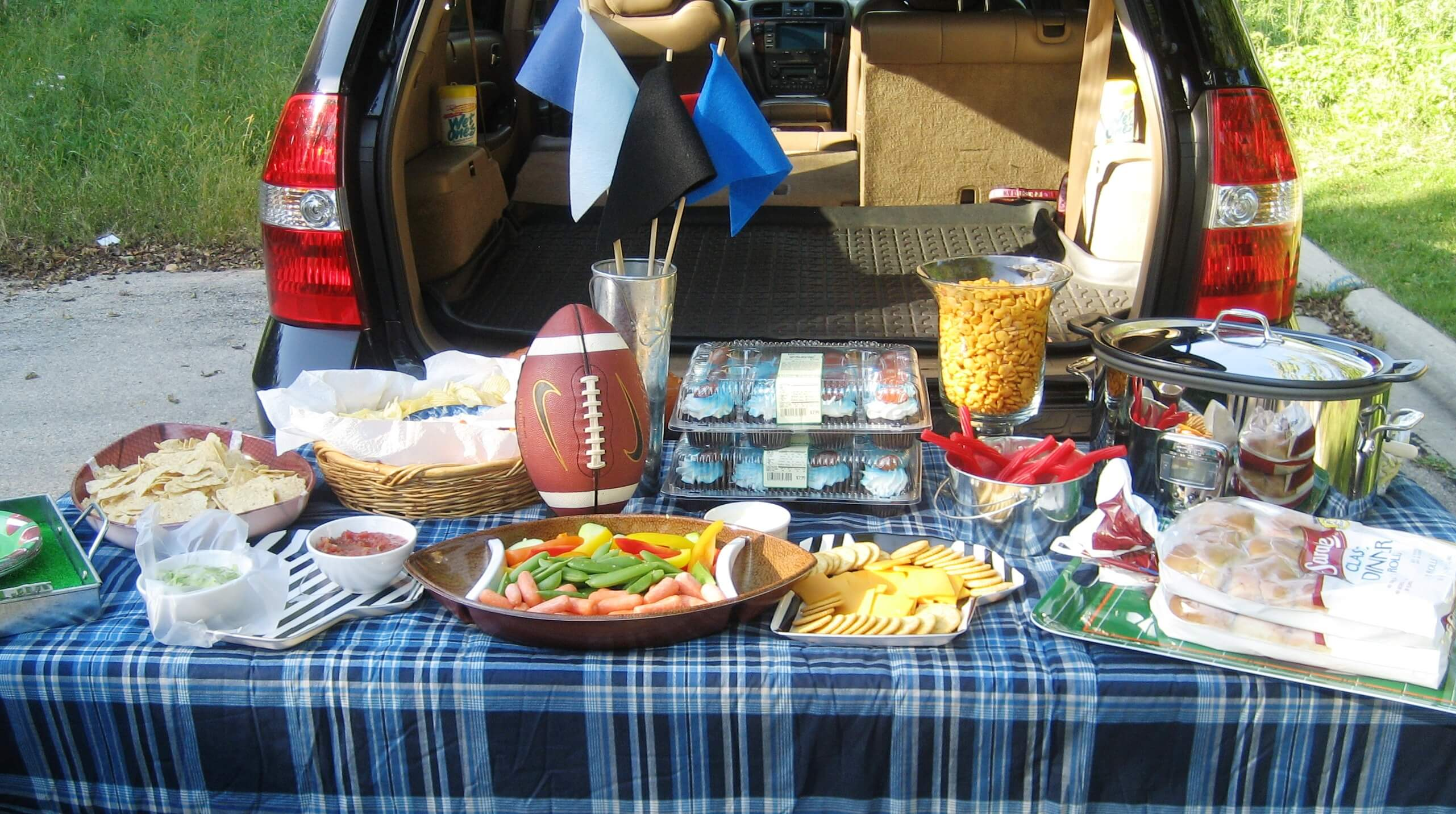 a tailgate of food such as cheese and veggies