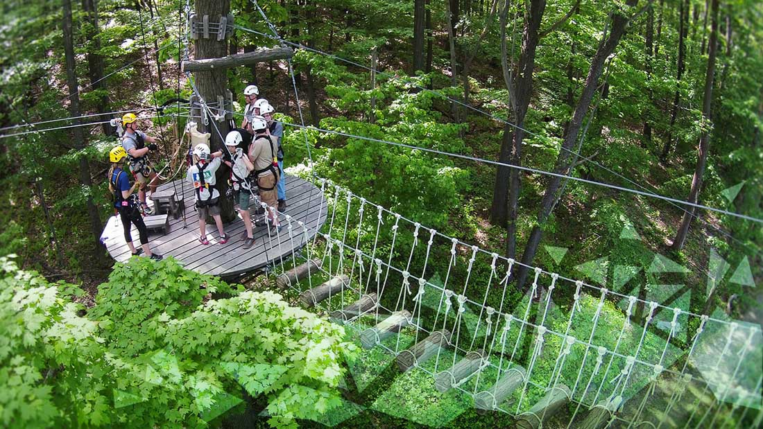 A group of people preparing to zipline from a tree stand