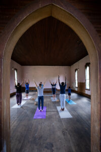 A Group of people doing yoga inside a rustic church