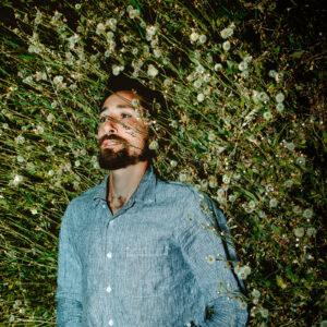 Album cover of a bearded man lying in a field of dandelions